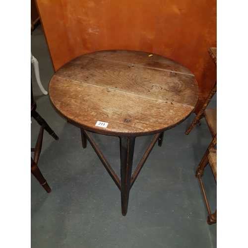 211 - A late 18/19th century oak cricket table with circular plank top on tapering legs joined by stretche...