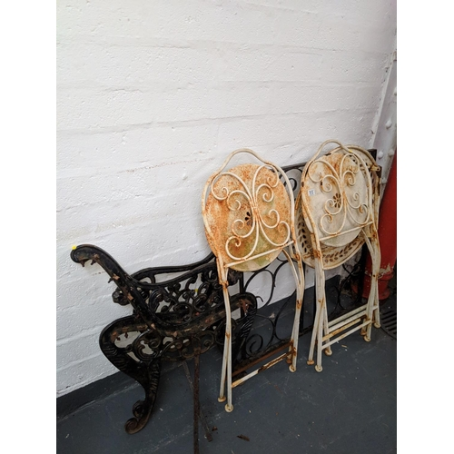 513 - A pair of cast iron bench ends and garden table with chairs...