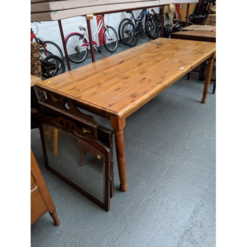 552 - A pine dining table and three wooden framed mirrors...