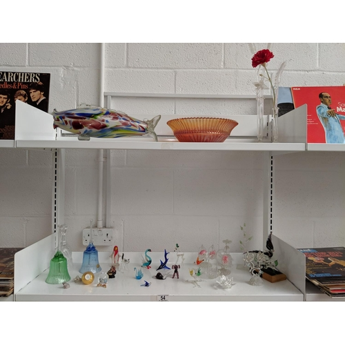54 - Two shelves of glass including glass animal figures...