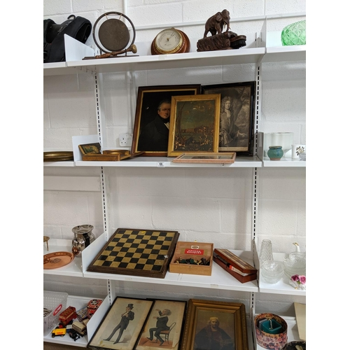 66 - Four shelves of mixed miscellaneous items including pictures, prints, chess set, wooden elephant sho...