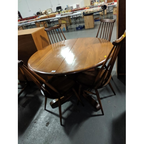 221 - An Ercol, circular, extending dining table and four chairs...
