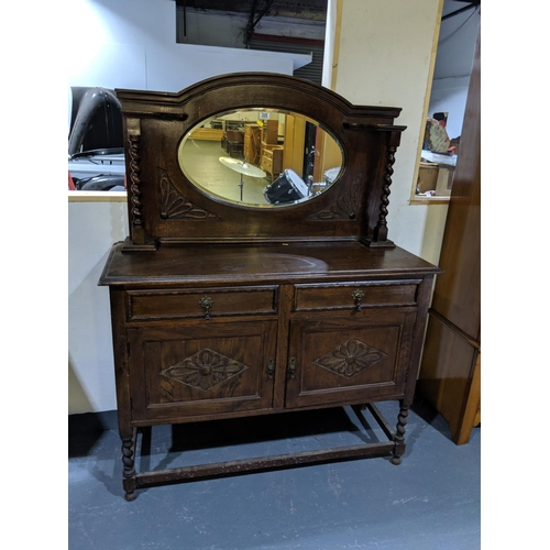 235 - An oak mirror backed sideboard...