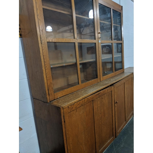 205 - An oak school cabinet with glazed top section...