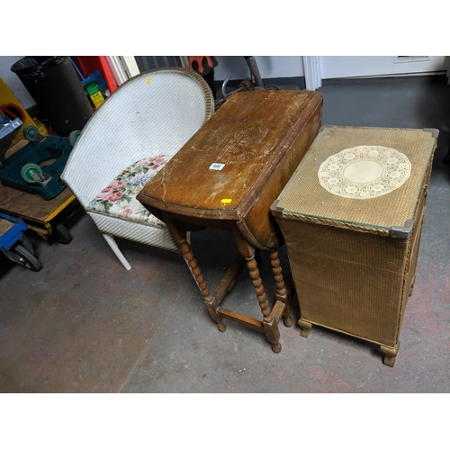 680 - An oak barley twist drop leaf table, loom style chair and laundry box...