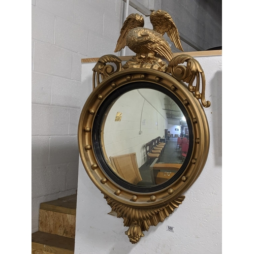 500 - A circular gilt framed convex mirror in the regency style with eagle...