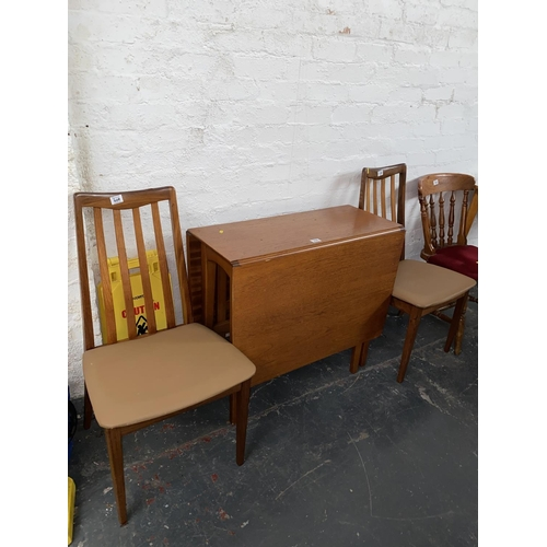 308 - A teak drop leaf table and two G Plan chairs...
