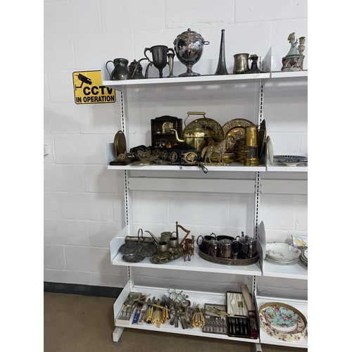 58 - Four shelves of mixed metalware including brassware, flatware and silver plated items etc.