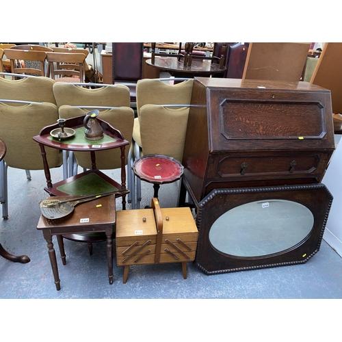 546 - An oak bureau, wine table, oak mirror, sewing box, small table, shelf unit and brassware