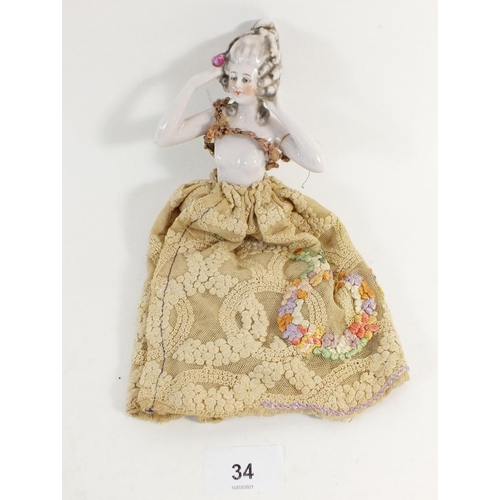 34 - A porcelain pin doll with net skirt, 12cm