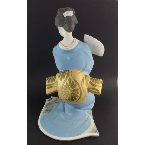 52 - A large Japanese painted bisque figurine of a Geisha with moveable fan, artists marks to base, 33.5c...