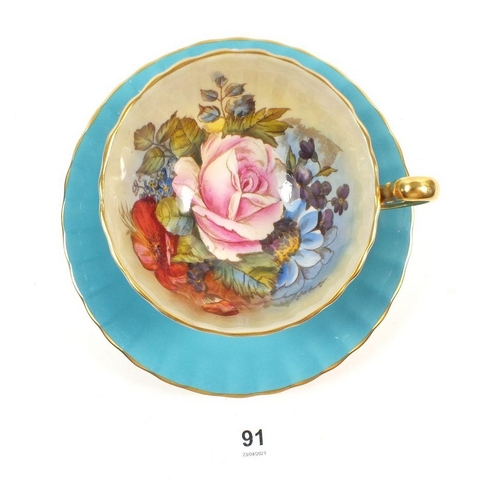 91 - An Aynsley turquoise blue cup and saucer printed flowers by J Bailey...