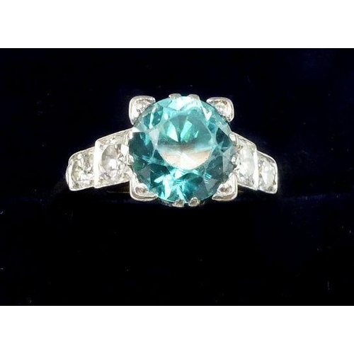 724 - A 1930's Art Deco 18 ct gold and platinum set ring set blue zircon flanked by four diamonds, size O,...