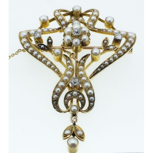713 - An Art Nouveau 15 carat gold diamond and seed pearl brooch with safety chain, 4.5cm length, 7.2g