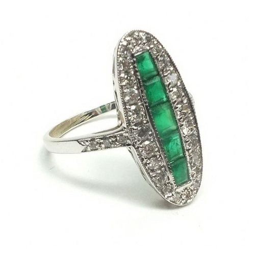 720 - An 18 carat white gold Art Deco style ring set line of five emeralds within long oval diamond surrou...