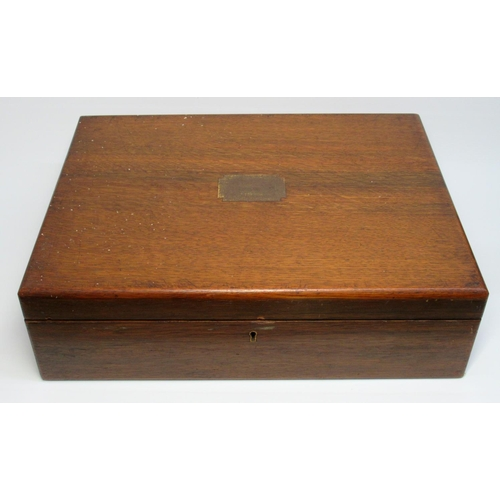 34 - A LARGE EDWARDIAN OAK CANTEEN WITH TWO INSET BRASS HANDLES AND VACANT CARTOUCHE, CONTAINING TWO TRAY...