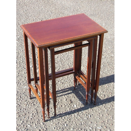 147 - A NEST OF THREE EDWARDIAN RECTANGULAR MAHOGANY TABLES EACH WITH A SATINWOOD CROSSBANDED TOP ON TURNE...