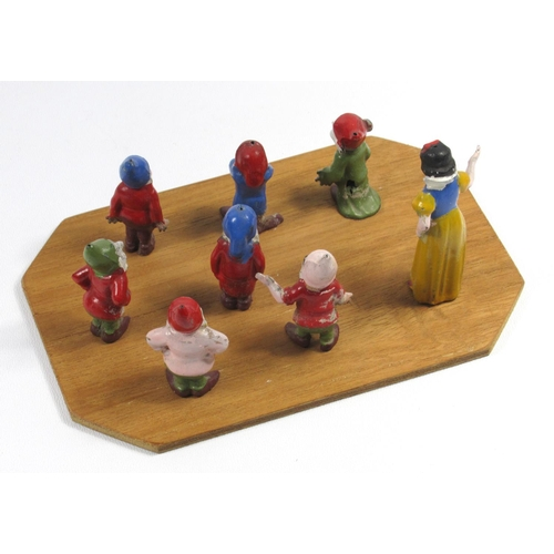 154 - VINTAGE ORIGINAL DIE CAST SNOW WHITE AND THE SEVEN DWARFS FIGURES MOUNTED ON A WOODEN PLINTH....