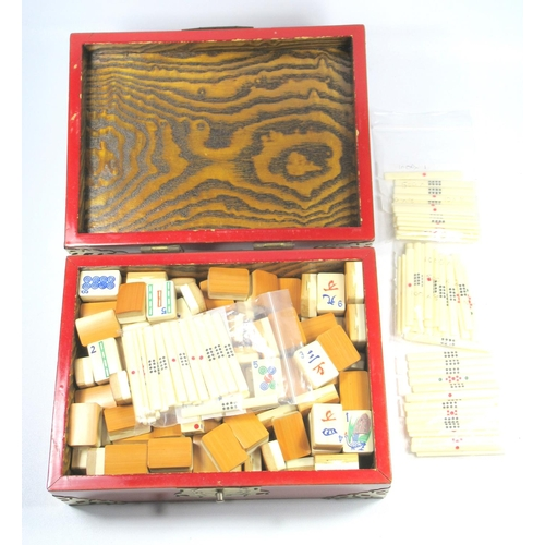 172 - MAH-JONG SET WITH BONE AND BAMBOO PIECES IN A RECTANGULAR RED LACQUERED BOX WITH BRASS MOUNTS (W. 24...