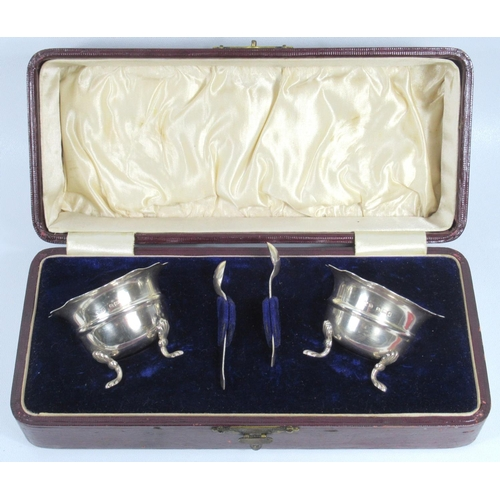 183 - PAIR OF EDWARDIAN SHAPED SALT CELLARS EACH ON THREE PAW FEET, WITH TWO SPOONS, BY W.D., BIRMINGHAM, ...