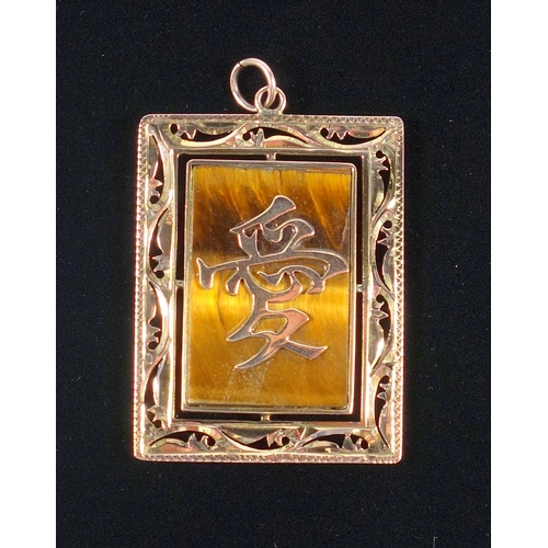 28 - ORIENTAL YELLOW METAL RECTANGULAR PENDANT SET WITH A TIGER'S EYE PANEL WITH APPLIED SCRIPT, WITHIN A...