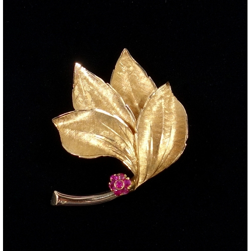 33 - YELLOW METAL LEAF BROOCH WITH A FLOWER SET SEVEN RUBIES (W. 4.7 CM), GROSS 8.1 GRAMS...