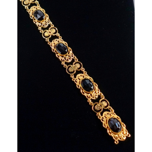 35 - YELLOW METAL PIERCED FLORAL AND SCROLL FANCY BRACELET, SET FIVE FACETED OVAL GARNETS, MARKED 585, GR...