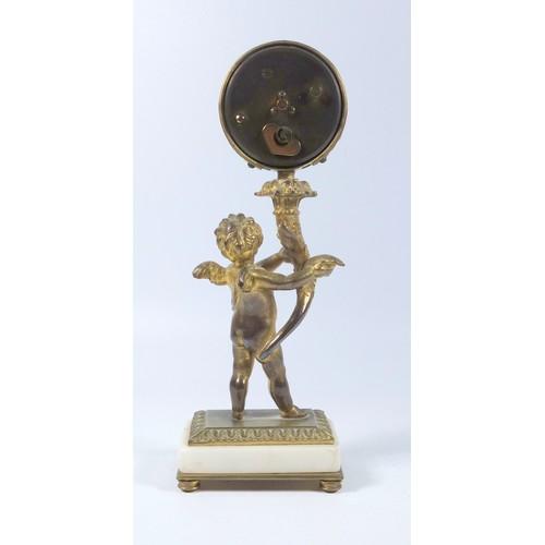 35 - FRENCH GILT BRONZE ALARM CLOCK WITH A CHERUB HOLDING A CORNUCOPIA SUPPORTING A CIRCULAR DIAL ENCLOSI...