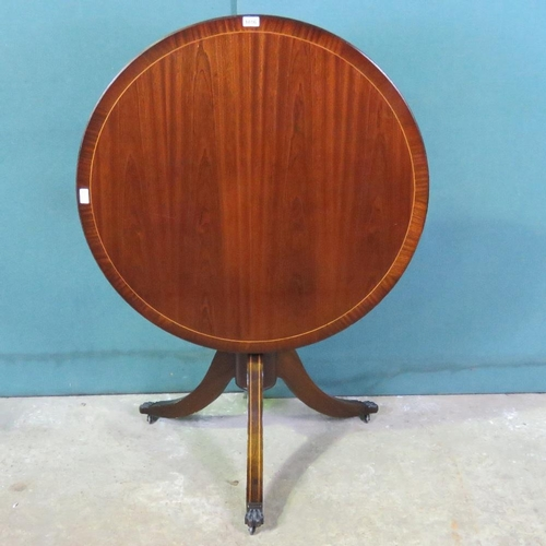1108 - A reproduction circular tilt top Georgian style table on triform base 92cm wide....