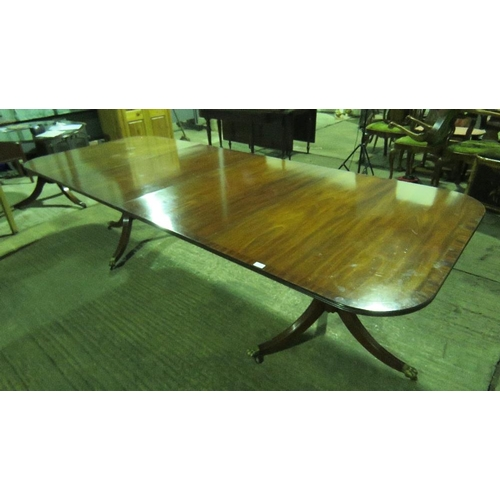 1118 - A reproduction Georgian style dinning table raised over two triform pillars and complete with two le...