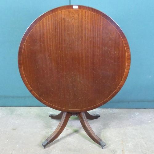 1124 - A reproduction circular tilt top Georgian style table on quatreform base 107cm wide....