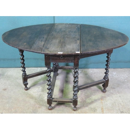 1139 - A c1930s oval drop leaf table raised over barleytwist supports. Together with another similar...