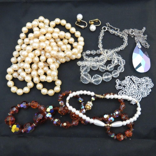 129 - A small collection of costume jewellery, mainly necklaces including a brown and a clear string of fa...