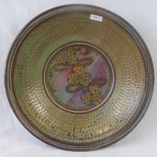 452 - A large, heavy and impressive hand made pottery charger of floral and abstract design, bearing name ...