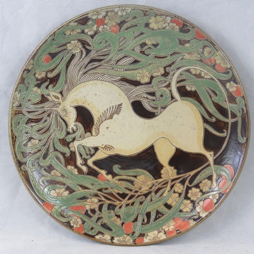 454 - A large contemporary studio charger depicting a Unicorn upon. Unmarked.  39.5cm diameter....