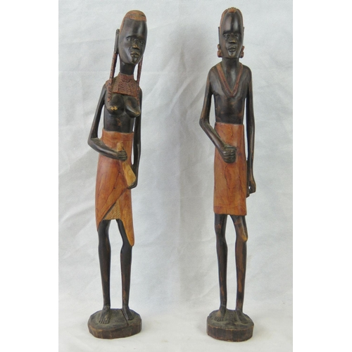 654 - A pair of 20th century ethnic hand carved tall African figurines being a man and a woman, 61cm high....