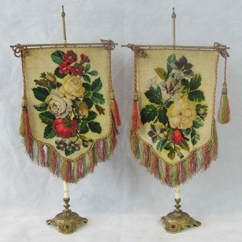 671 - A pair of unusual Edwardian table screens. Fine needlepoint screens with floral decoration on a gilt...