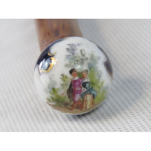 672 - A mahogany walking cane surmounted by a spherical ceramic hand painted globe handle depicting pastor...