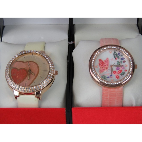 264 - Watches. Two bedazzled watches with painted dials. One with white patent strap and heart design, and...