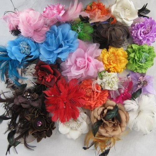 319 - Brooches/stick on flower and feather arrangements. Approx twenty-four in mixed colours....
