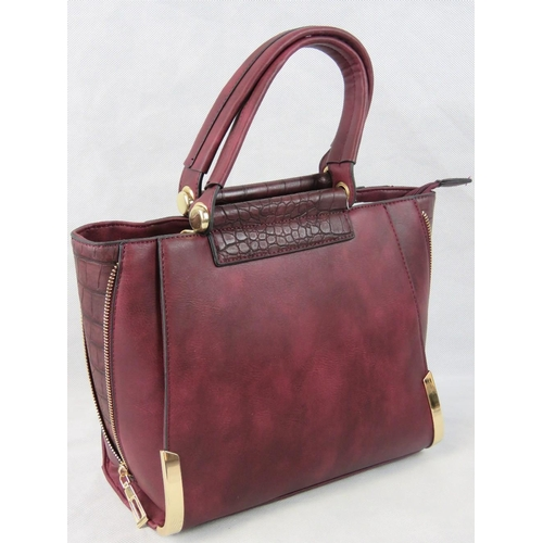 32 - Handbag. Burgundy with zip detail to sides, two handles, zip closure, two internal zip pockets and t...