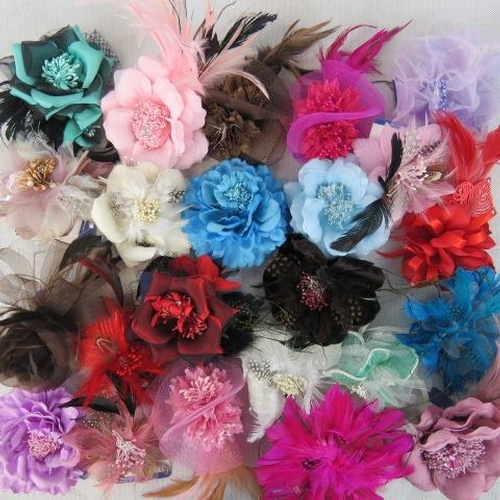 320 - Brooches/stick on flower and feather arrangements. Approx twenty-four in mixed colours....