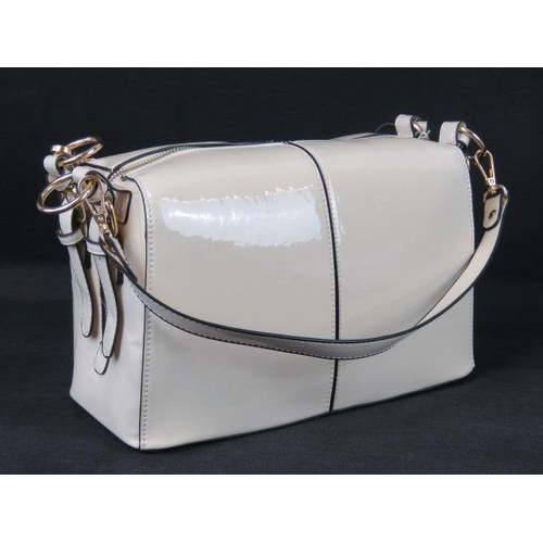 334 - Handbag. Cream patent with buckle detail to sides, two detachable handles, two way zip closure, inte...
