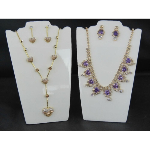 364 - Costume Jewellery. Two necklace and earring sets. One with heart design and one with lilac and white...