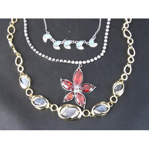 378 - Costume Jewellery. Three necklaces. One red flower and white stone encrusted chain, one blue opalesc...