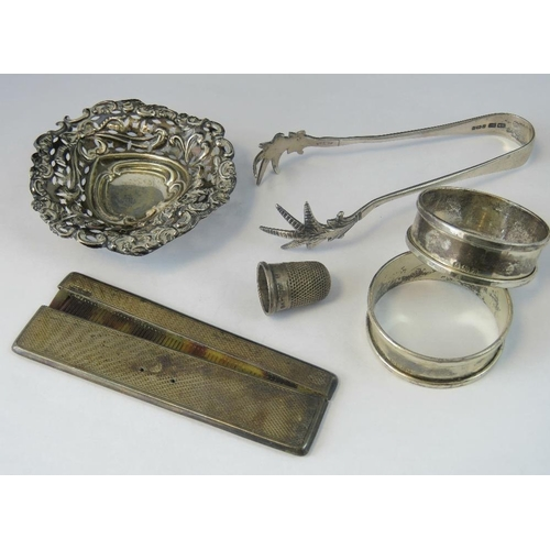 11 - HM silver items; a pair of napkin rings, Birmingham 1947, a pair of sugar tongs with birds claw term...