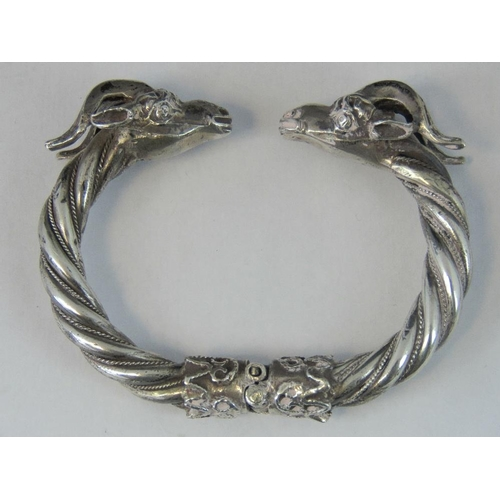 136 - A hinged 900 silver bangle with goat head terminals, bolt locking mechanism in hinge, stamped 900, 2...
