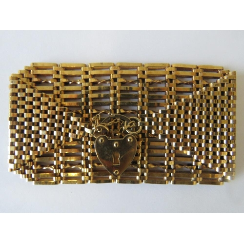 149 - A yellow metal sixteen bar gate bracelet with heart padlock....