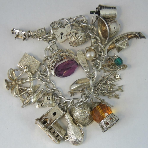 163 - A silver charm bracelet with heart clasp, eighteen charms, some marked silver or hallmarked and some...