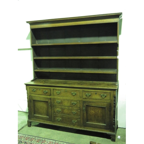 1123 - A Georgian oak dresser, three-shelf rack top with pediment over, the base with single central door a...